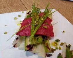 saumon coloré à la betterave sur lit d'asperges croquantes, pousses de blé et pistaches